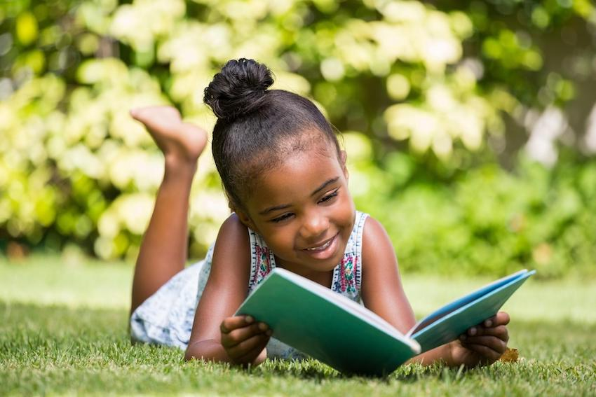 Summer learning loss: Little girl reading a book while laying on the grass