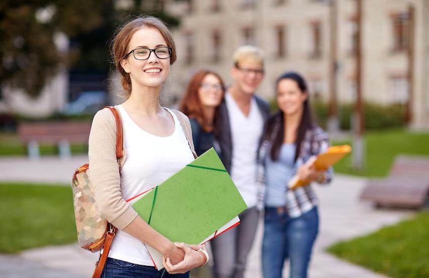 FAFSA questions: College student smiling infront of the school building
