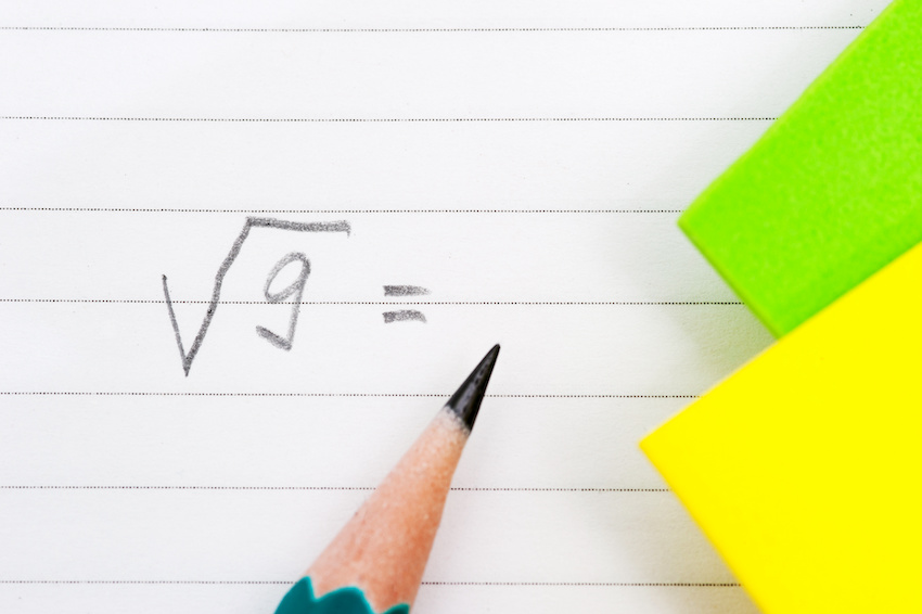 how to square a number: square root formula on a notebook with a pencil nearby