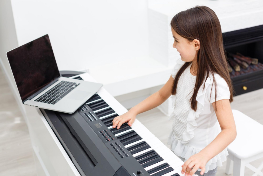 Music tutor: Young student playing the organ at home during online class
