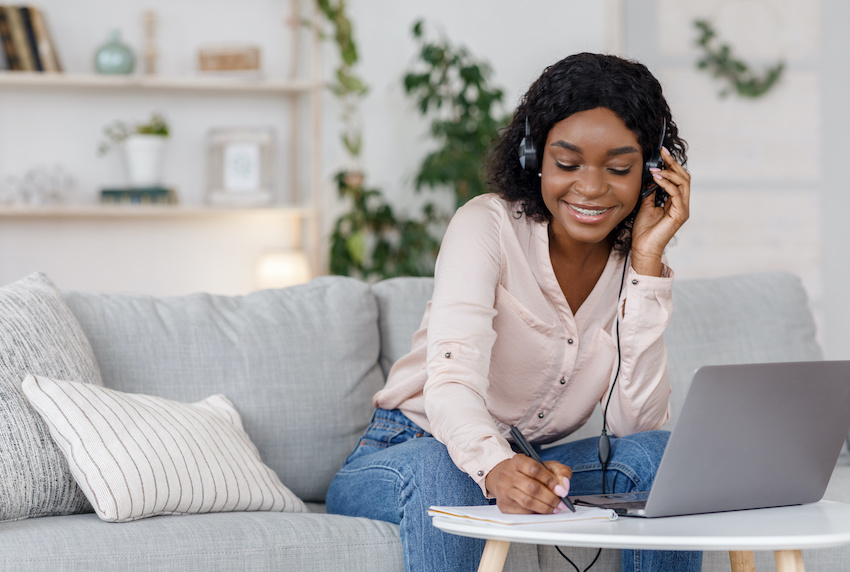 Accounting tutor: A student listens to her computer with headphones and writes notes