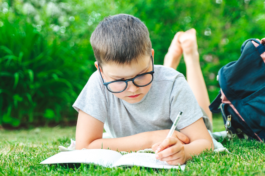 boy dividing fractions with whole numbers while laying on the grass