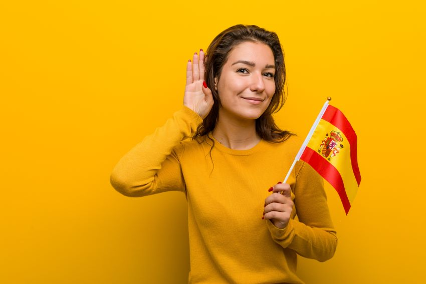 Young woman holding a Spanish flag and cupping her hand around her ear