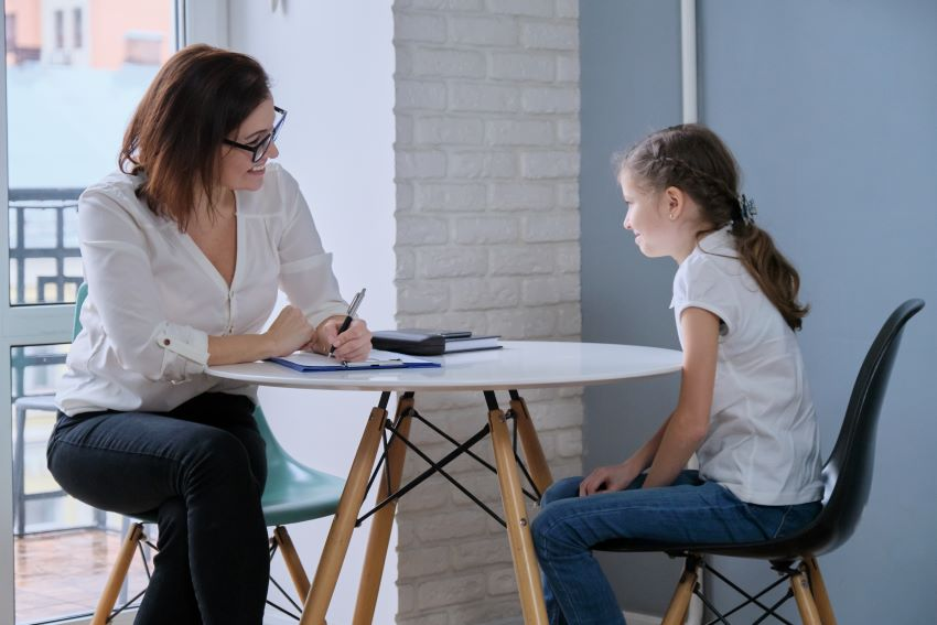 School professional talking with a young girl at a table
