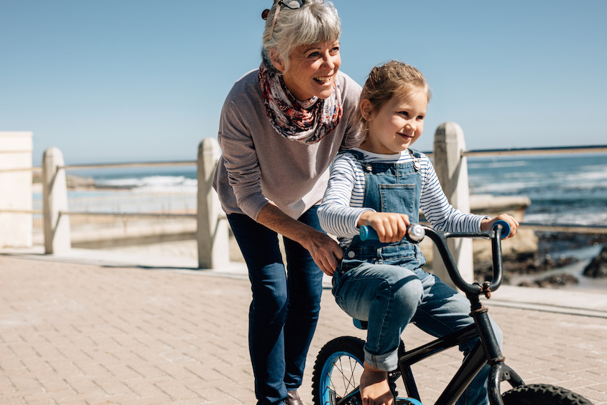 Summer learning loss: Grandmother teaching little girl how to ride a bike