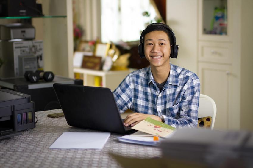 Teenager doing schoolwork at home using his laptop