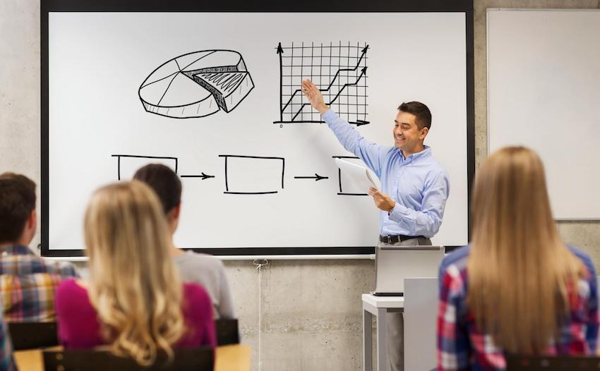 Econ tutor in front of a class pointing at graphs on a whiteboard