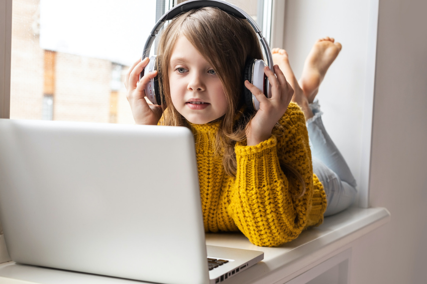What is distance learning: A little girl with headphones using a laptop
