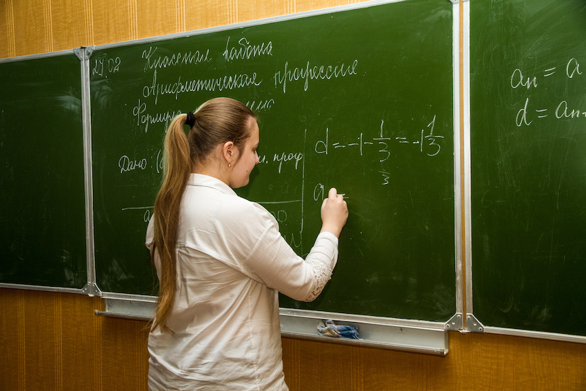 Teenager solving an equation on a blackboard