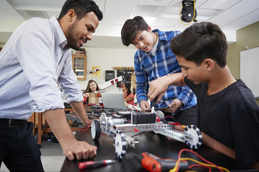 Science tutor: Teacher with male students building robotic vehicle in the classroom