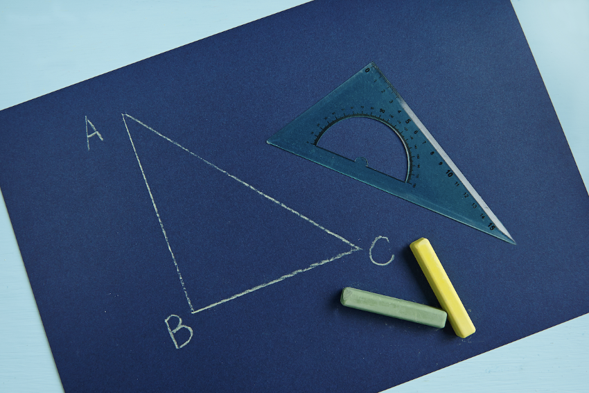 how to find the measure of an angle: Chalk drawn triangle with a triangle ruler and chalks over a blue board