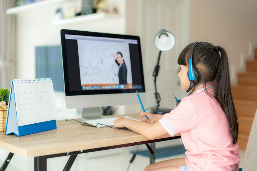 Young female student having a video conference with her teacher on computer