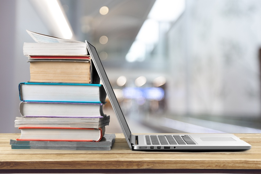 A stack of books next to an open laptop on a desk