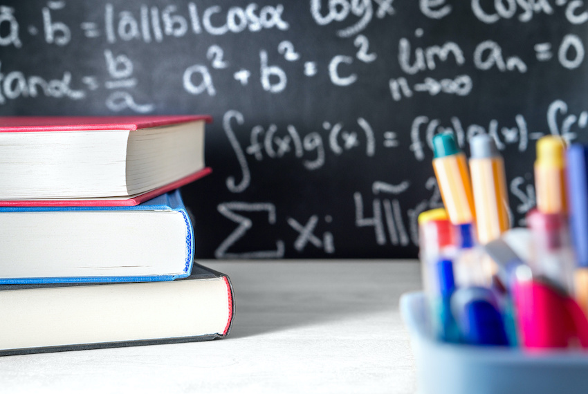 SAT math tips: a stack of books, school supplies, and a blackboard covered in math problems