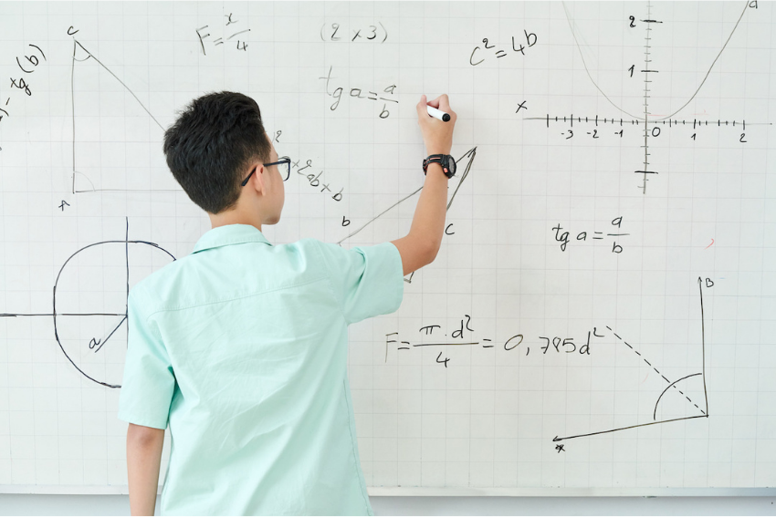 Geometry tutor: A male student writing equations on whiteboard
