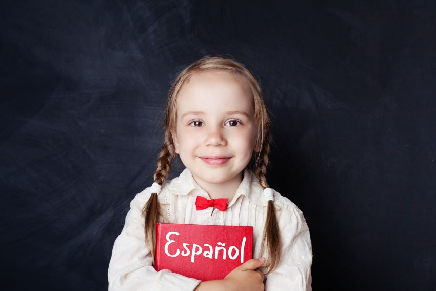 Child smiling and holding book that helps her study Spanish