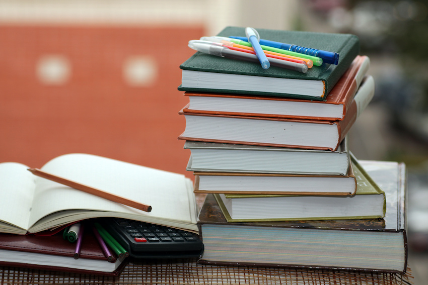 A stack of books, a calculator, a notebook, and pens