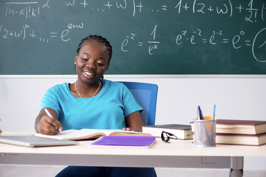 scientific notation definition: Smiling woman writing on a notebook with a blackboard behind her