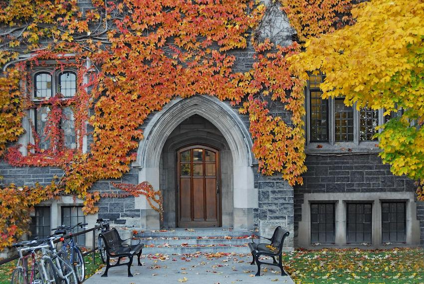 Apply for FAFSA: College building doorway with fall leaves and bikes