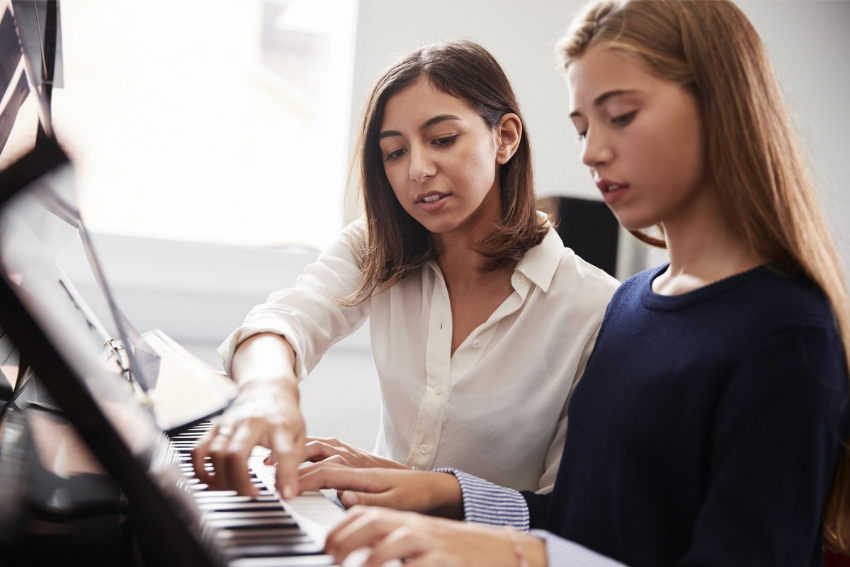Music tutor: A female student with her teacher playing the piano