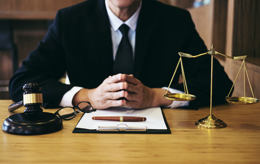 LSAT logical reasoning: A lawyer with a clipboard, scales of justice, and a judge's gavel