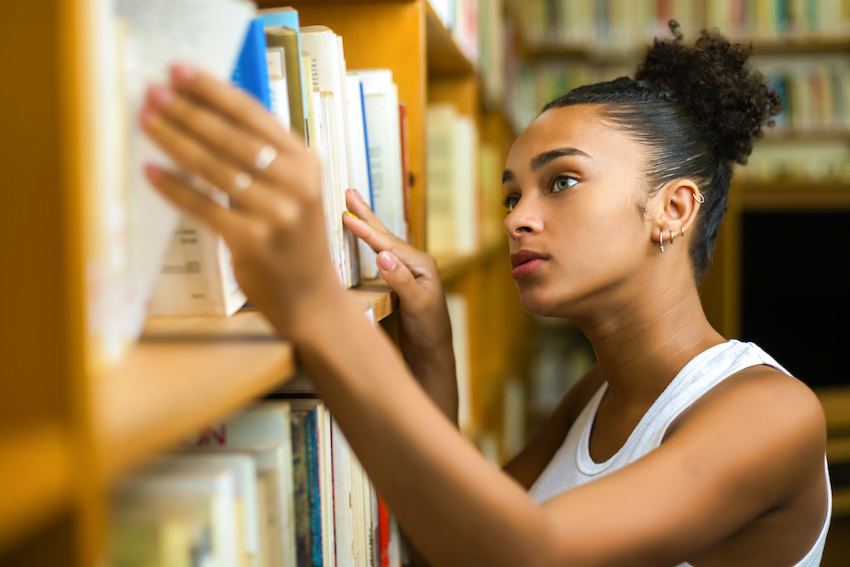 Best ACT prep book: A high school student looks through books on a library shelf
