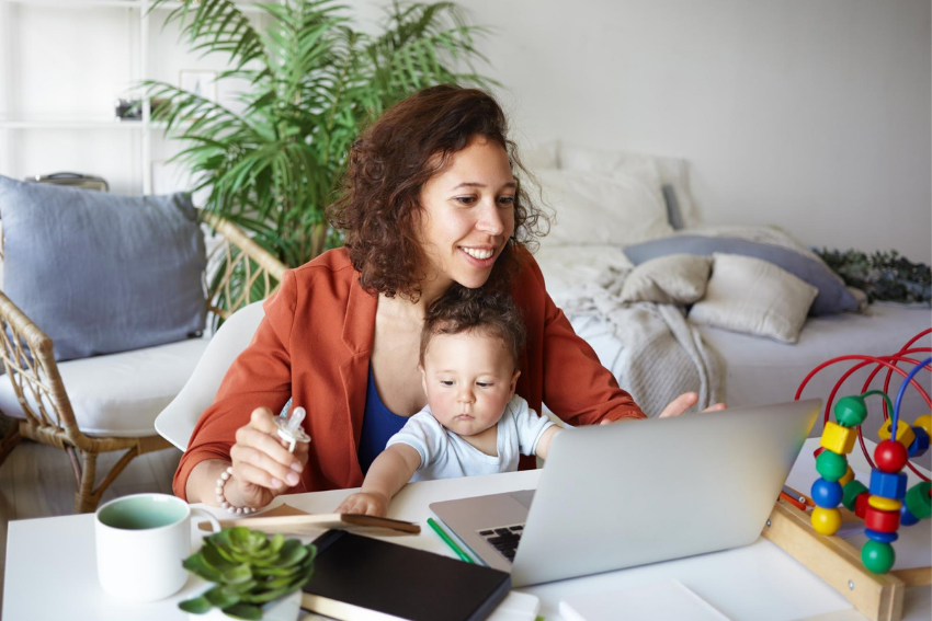 What is distance learning: A woman in front of a laptop with her baby on her lap