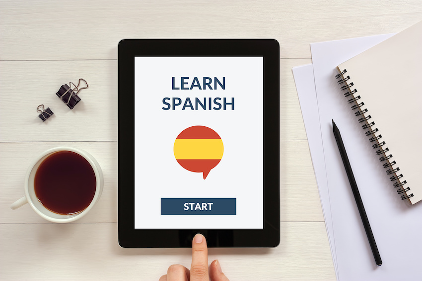A hand clicks a button on a tablet to start a session with an online Spanish tutor