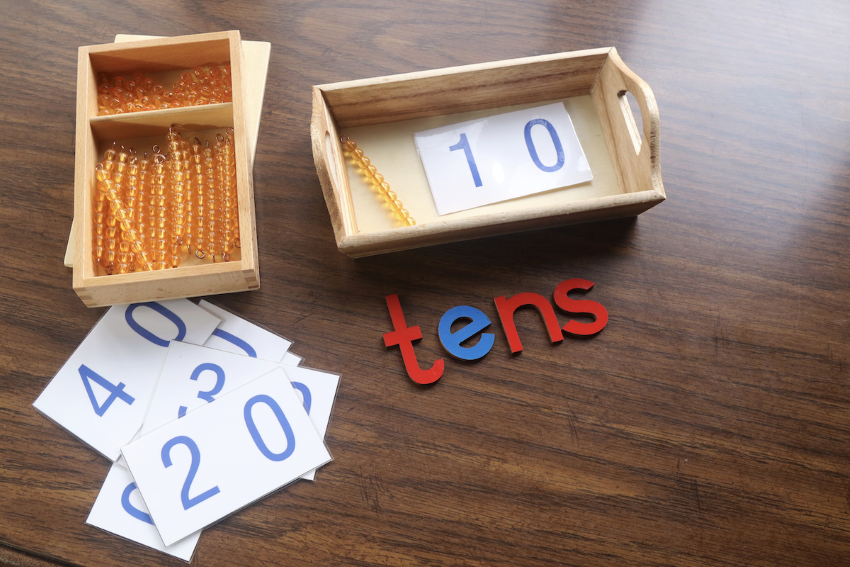 powers of 10: Box of beads, number cards and letter cutouts on a wooden surface