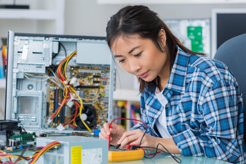 Computer science tutor: A female student fixing a computer hard drive