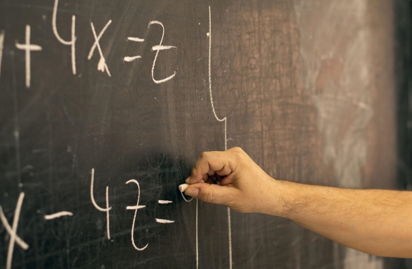 two-step equation example: Person writing a mathematical equation on a blackboard