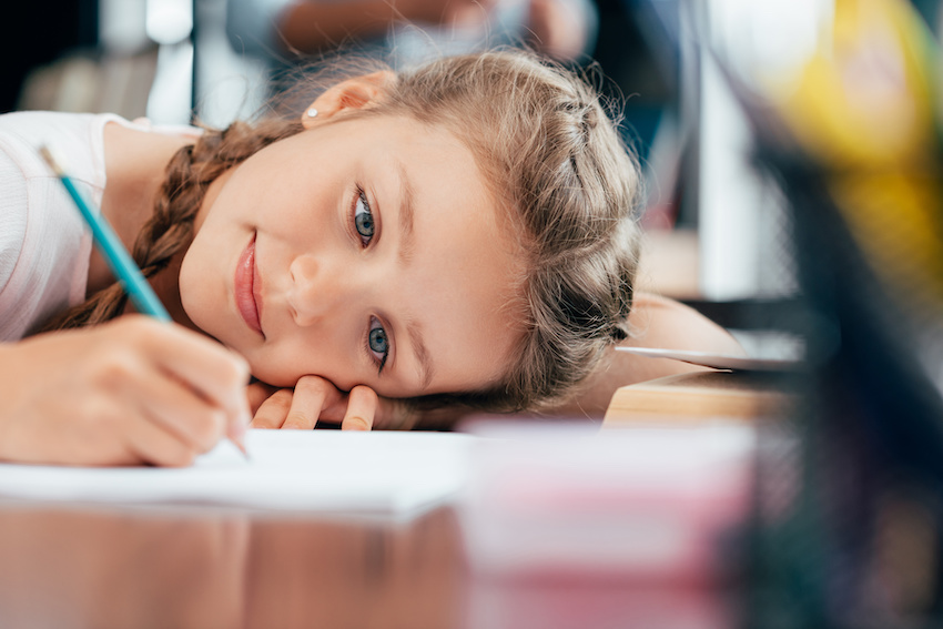 A student works on her math homework with her head resting on the desk