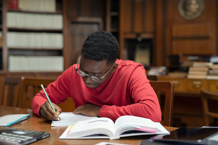 Best ACT prep book: A student studying in the library with a test book