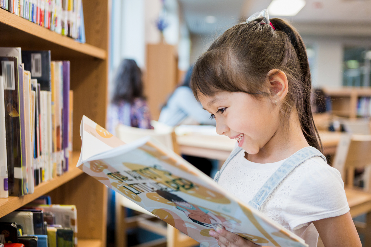 young child begins reading picture book