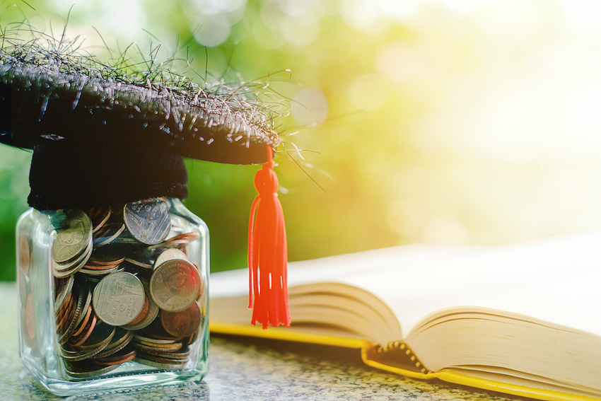 How much should you pay a tutor per hour: A jar of coins topped with a graduation cap
