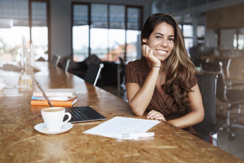 Young woman sitting with a laptop to study Spanish in a coffee shop