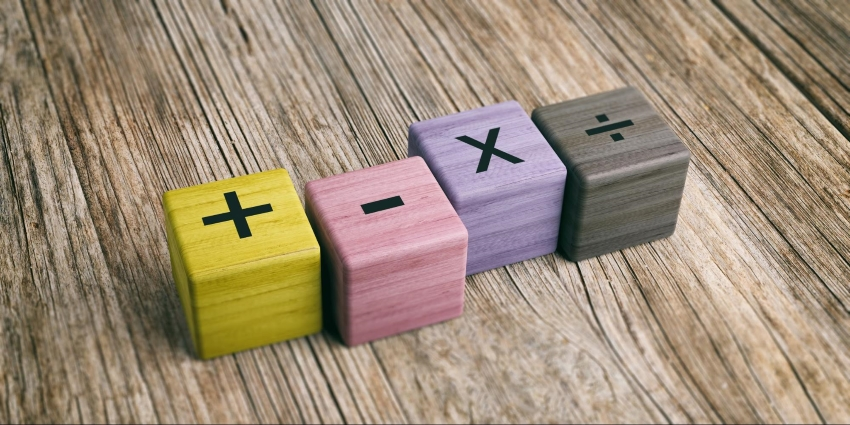 what does PEMDAS stand for: Colored blocks with mathematical symbols on top of a wooden surface