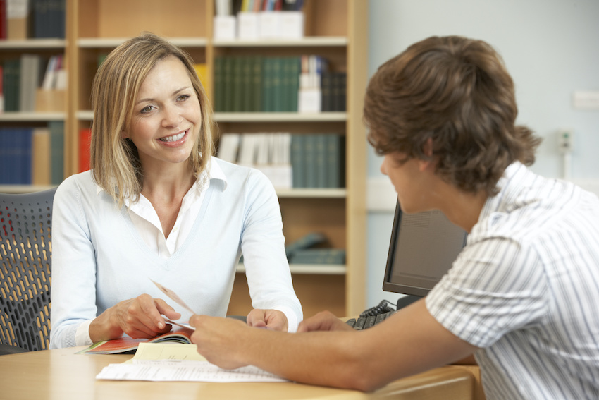 In-person vs. online tutor: A college student works with an in-person tutor in the library