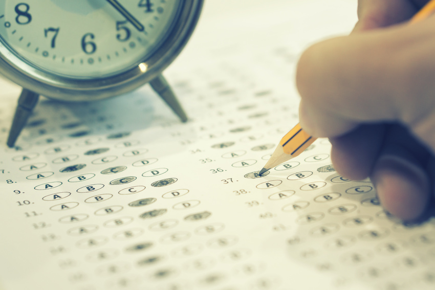 How long is the SAT test: A hand fills in a scantron next to an alarm clock