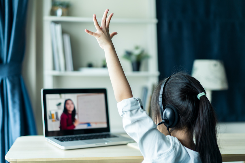 In-person vs. online tutor: A student raises her hand in front of a virtual classroom