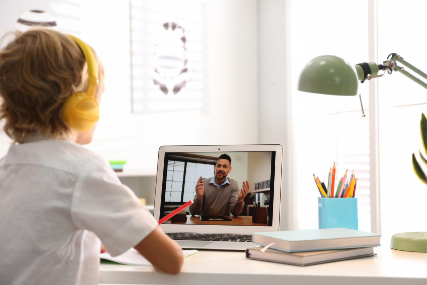 Young male student learning via video conference with his teacher
