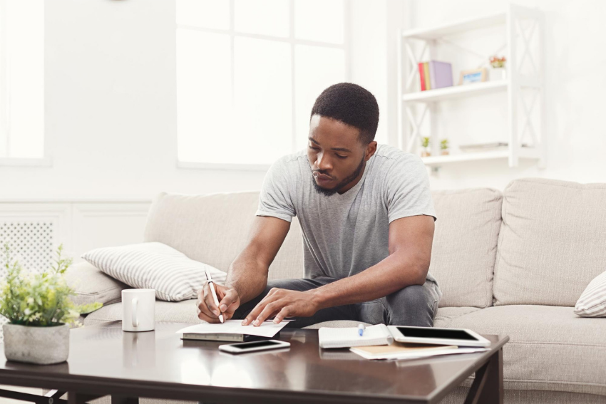 What is distance learning: A young man sitting on the couch and writing on a table