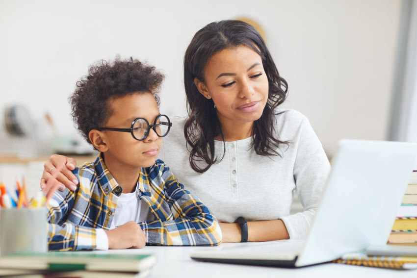 Find a tutor: Black boy using a laptop with his mom
