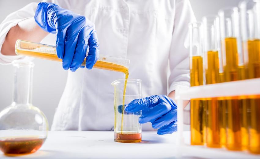 A scientist pours chemical compounds from a test tube to a beaker