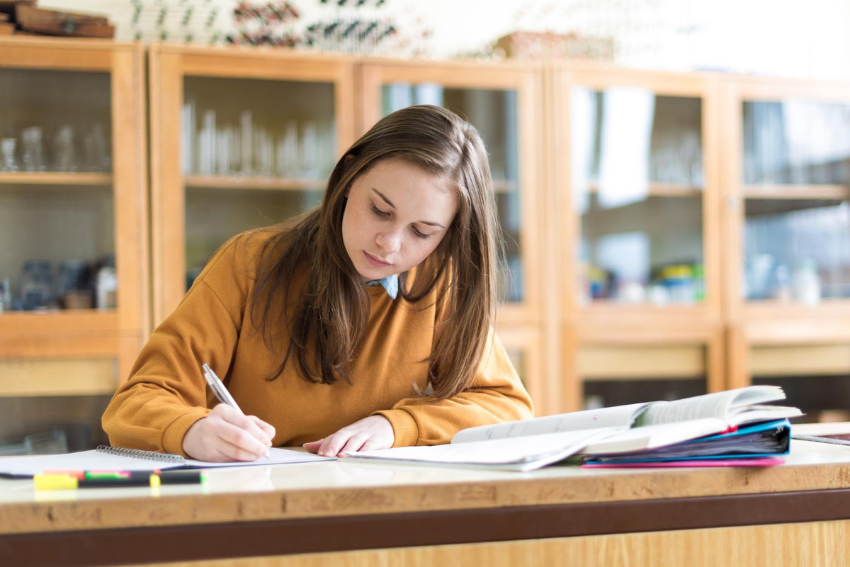 Female student writing notes on her notebook