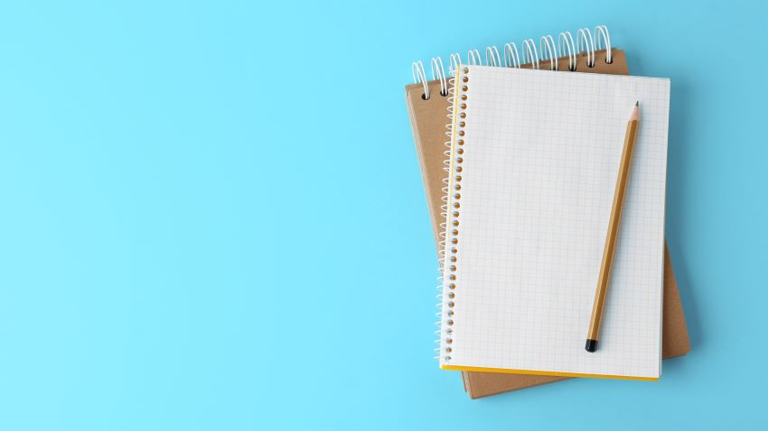 Notebooks with pencil on light blue background
