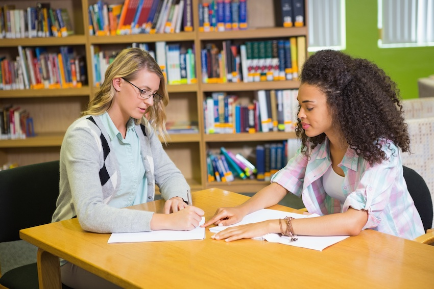 In-person vs. online tutor: A student works with a tutor in a library
