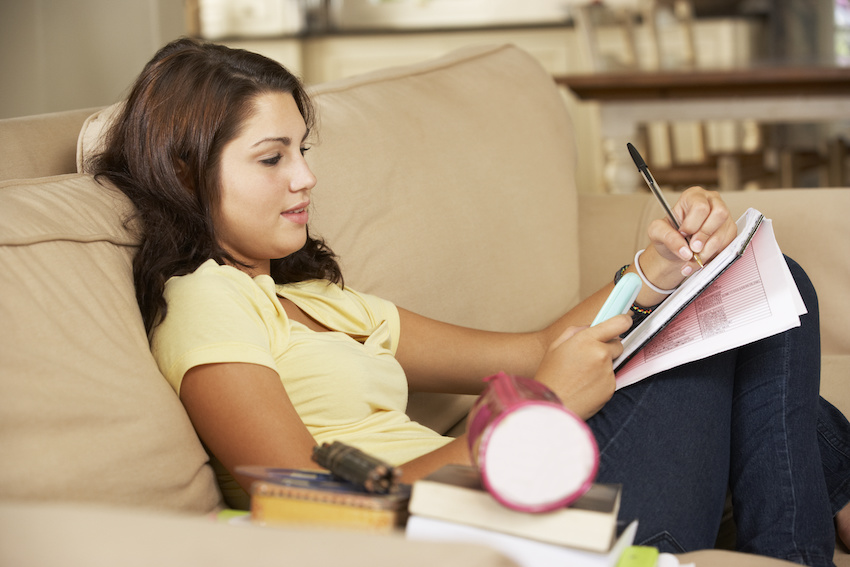 Mean median and mode: teenanger sitting on a sofa and doing her homework