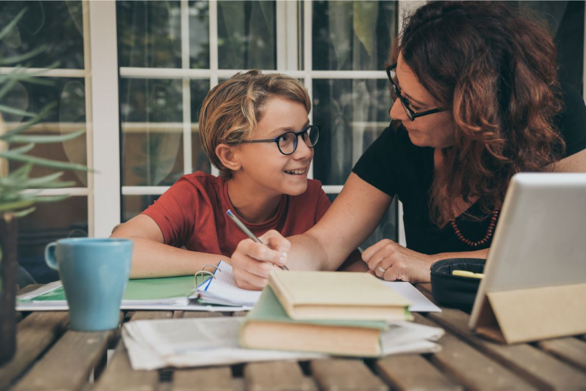 Home school tutoring: Mother helping his son do his homework at home