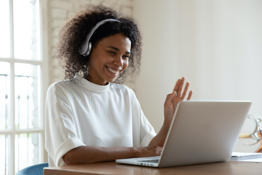 An online English tutor interacts with her computer screen